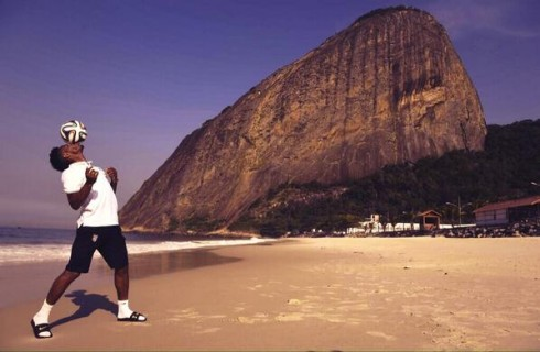 Raheem Sterling playing keeping uppy on the beach in Rio, with Sugarloaf Mountain behind